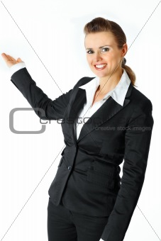 Smiling modern business female presenting something on empty hand