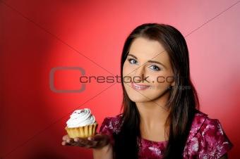 young beautiful girl eating small sweet cake.