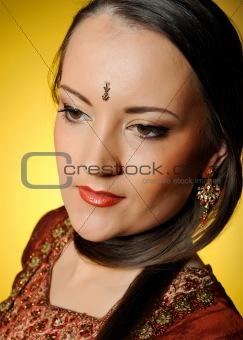 Young beautiful woman in indian traditional jewellary, bindi and sari dress. yellow background