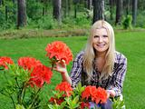 Beautiful gardener woman with red flower bush outdoors