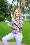 Pretty gardener woman with gardening tools outdoors. greenhouse