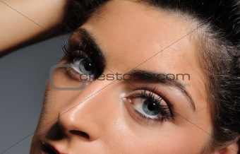 Beautiful macro shot of blue eyes with long lashes and make-up