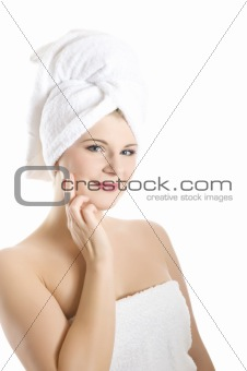 beautiful young woman in bath towel touching her skin