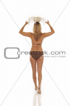 Back view of woman holding surfboard