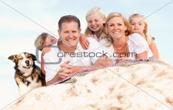 Happy Caucasian Family and Dog Portrait at the Beach One Sunny Afternoon.