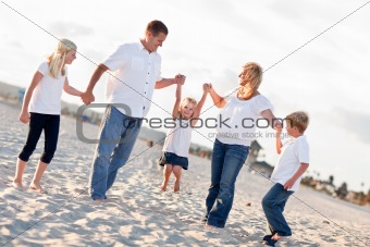 Adorable Little Girl Swinging with Her Parents and Family at the Beach.