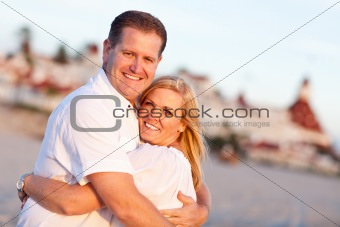 Attractive Caucasian Couple Hugging at the Beach in Front of the Hotel Del Coronado, San Diego, CA.