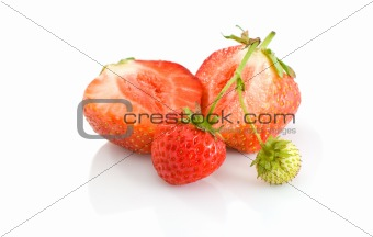 One green, unripe and pair of ripe red strawberries, with one cutted on half