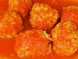 Meatballs in tomato sauce on white dish.