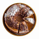 Ring shaped chocolate cake on ceramic tray.
