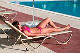 A beautiful young girl in a bikini sunbathing on a lounger near the hotel swimming pool under parasol