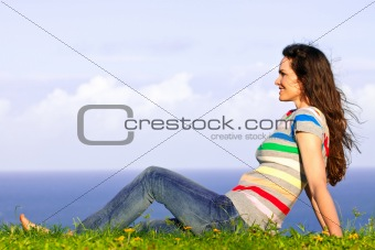 Beautiful young happy woman relaxing in the grass by the ocean