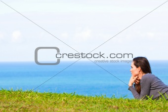 A sad and depressed young woman lying in the green grass by the ocean