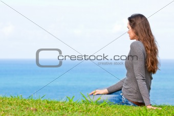 Sad and upset young beautiful woman sitting by the ocean