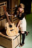 beautiful young woman with a classical guitar in a warehouse with boxes like scenario