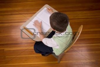 Boy writting at school desk