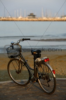 Classic bicycle parked on the seafront at sunset