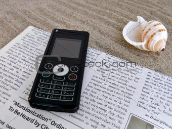 Close up shot of newspaper, celfone, shell on the sand