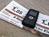 Close up shot of celphone and newspaper on the sand