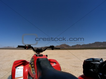 ATV on dry lake bed against mountains and clear blue sky