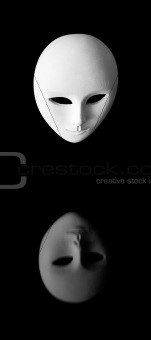 beautiful white venetian mask admiring itself in mlack mirror surface - narcissism concept