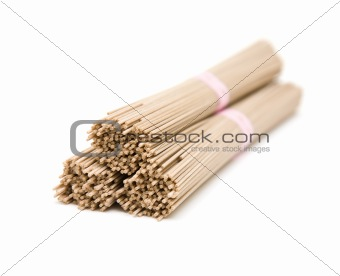 Three stacked bundles of Japanese buckwheat soba noodle; isolated on white background