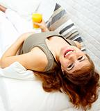 Smiling beautiful pregnant woman relaxing on sofa with glass of juice  in hand