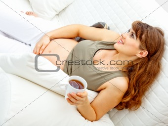Smiling beautiful pregnant woman relaxing on sofa and  holding cup of tea in hand