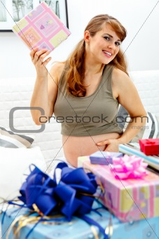 Smiling  beautiful pregnant woman sitting on couch with gifts for her unborn baby