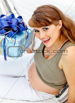 Smiling  beautiful pregnant woman sitting on couch with present for her  unborn baby