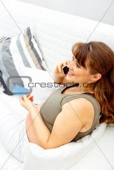 Smiling beautiful pregnant woman with mobile phone and credit card on sofa