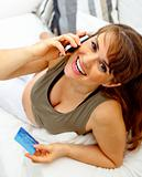 Smiling beautiful pregnant woman with mobile phone and credit card on couch