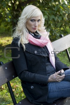 blond girl sitting in a bench