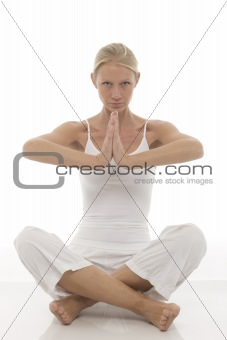 a young caucasian woman dressed in white sitting cross-legged doing yoga