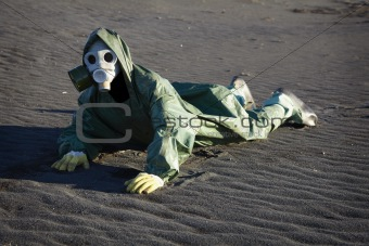 Man in gas-mask on desert ground