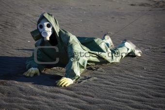 Man in gas-mask on desert ground