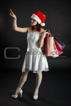 Woman in New Year's cap chooses purchases and gifts