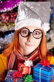 Funny girl in christmas cap with gift boxes