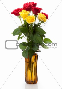 A bouquet of beautiful long red and yellow roses with large green leaves in a glass vase on a white background