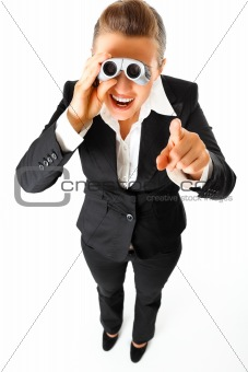 Interested modern business woman with  binoculars and  pointing finger at you