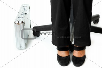 Briefcase at legs  of business woman sitting on chair