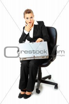 Sitting on chair surprised  modern business woman looking in suitcase