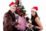 happy young couple, opening gifts beside Christmas tree, isolated on white