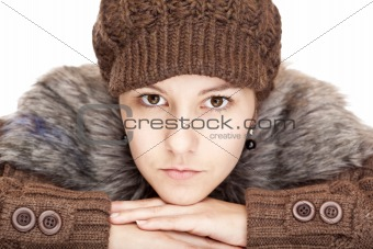 Beautiful young woman with pullover and cap looks serious.
