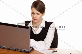Young business woman sits on desk and works on laptop