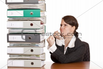 Business woman holds fists to file folder stack