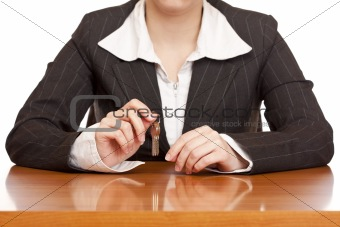 Business woman holds house key for handing over of keys