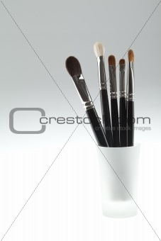 a set of 5 make-up brushes set in a small glass
