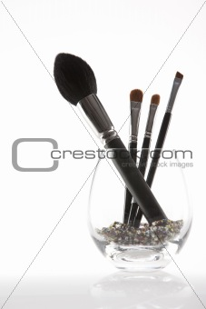 a set of 4 make-up brushes in a transparent glass
