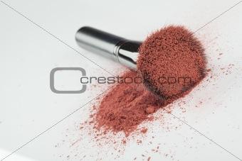 a blush brush, with pink loose blush